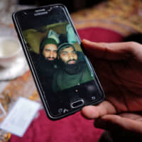 Bilal Ahmad Naikoo shows a photo of his brother Hilal with Rashid Bhai, a Pakistani and fellow member of Jaish-e-Mohammed, on March 21 in Pinglan in Kashmir. | REUTERS