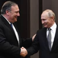 Russian President Vladimir Putin and U.S. Secretary of State Mike Pompeo greet each other prior to their talks in the Black Sea resort city of Sochi, southern Russia, on Tuesday.  | POOL / VIA AP