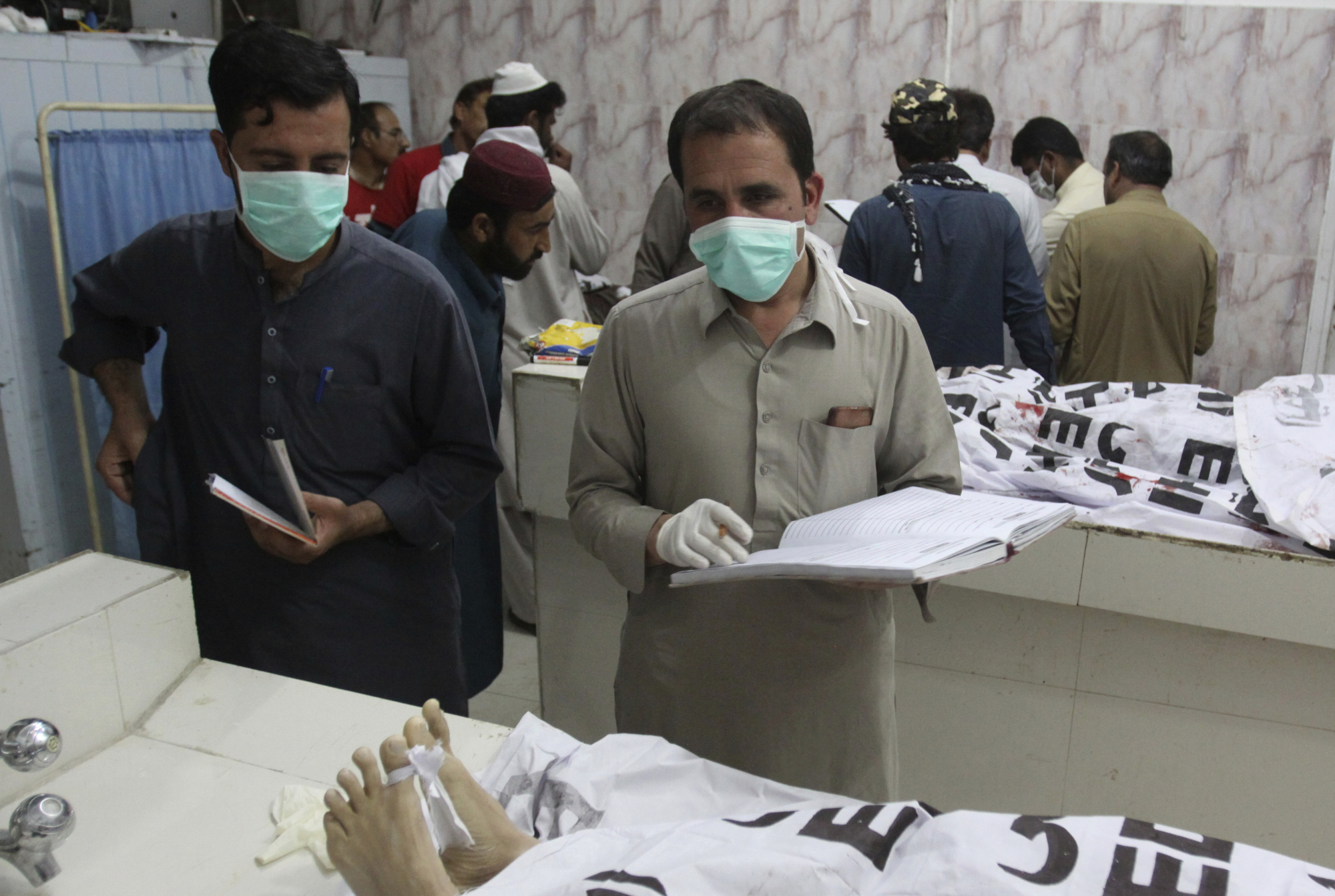 Pakistan hospital staff collect information on alleged terrorists killed by security forces, at a mortuary in Quetta, Pakistan, Thursday. Pakistani police say security forces acting on intelligence raided a militant hideout in the town of Mastung in southwestern Baluchistan province, triggering a shootout that killed many suspects. | AP