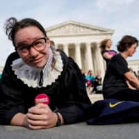 Alice Wisbiski, 22, a supporter of Ruth Bader Ginsburg, performs exercise planks in celebration of the Supreme Court associate justice's 86th birthday in Washington March 15. | REUTERS