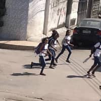 In this photo released by Leonardo Alves, students run from their school during a shootout between police and suspected drug traffickers in the Mare shantytown of Rio de Janeiro Monday. Brazilian officials say an anti-crime operation by police resulted in eight people being killed during the shootout. | AP