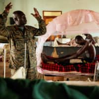 A South Sudanese militar chaplain prays during a visiting to soldier at Juba Military Hospital on April 27. Despite a ceasefire arrangement signed by the government and the opposition forces last year, violence and interethnic fights have continued within the country. | AFP-JIJI