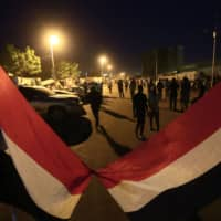 Sudanese gather as protests continue near Sudan's military headquarters in central Khartoum on Monday. Sudan's protest leaders said they have reached a breakthrough agreement with the country's military rulers on transitional authorities to run the country. The news came shortly after the prosecutor general's office said ousted President Omar al-Bashir had been charged over the killings of protesters during anti-regime demonstrations. | AFP-JIJI