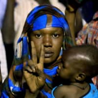 A Sudanese woman holding a baby flashes the 'V' for victory sign as protesters gather outside the military headquarters in Khartoum demanding the instalment of civilian rule on Monday. Thousands of Sudanese men and women have held an around-the-clock sit-in at the site since April 6, initially to seek the military's support in toppling longtime autocrat Omar Bashir and later to remove the generals who seized power after his ouster. | AFP-JIJI