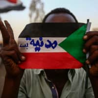A Sudanese protester holds the national flag with writings reading in Arabic 'Civilian Only' during a rally outside the army headquarters in Khartoum May 2. The U.S. pressed Sudan's military leader Wednesday to reach an agreement with protesters, who have threatened a disobedience campaign unless there is a transfer to civilian rule. | AFP-JIJI