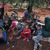 Displaced Syrians gather under a tree in a field near a camp for displaced people in the village of Atme, in the jihadi-held northern Idlib province, on Wednesday. Bombardment by the regime and its Russian ally on northwestern Syria has displaced nearly 140,000 people since February, the U.N. said. | AFP-JIJI