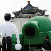 Giant balloons in the shape of a Chinese military tank and 'Tank Man' are seen in front of Chiang Kai-Shek Memorial Hall in Taipei on Tuesday, ahead of 30th anniversary of the 1989 military crackdown on pro-democracy protesters in Beijing's Tiananmen Square. | REUTERS