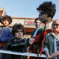 An actor dressed as Tyrion Lannister poses for photographers with a fake severed head before the screening of final episode of 'Game of Thrones 'on a 20-meter-high screen at RZD Arena in Moscow Monday. | REUTERS