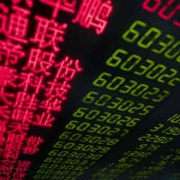 Stock price movements are seen on a screen at a securities company in Beijing on Monday. China's key stock indices plunged more 5 percent the same day after U.S. President Donald Trump threatened to hike tariffs on Chinese imports, potentially derailing high-level trade talks as they enter their final phase. | AFP-JIJI