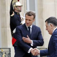 French President Emmanuel Macron welcomes Libyan Prime Minister Fayez Al-Sarraj, who heads the U.N.-backed government in Tripoli, at the Elysee Palace in Paris Wednesday. | REUTERS