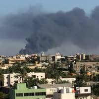 Smoke rises during a fight between members of the Libyan internationally recognized government forces and eastern forces in Ain Zara, Tripoli Sunday. | REUTERS