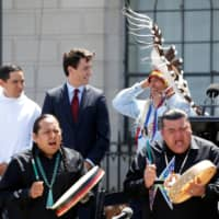 Canadian Prime Minister Justin Trudeau (second, left) and Assembly of First Nations National Chief Perry Bellegarde (second, right) react to the wind during an event announcing the creation of a new space for Indigenous Peoples at 100 Wellington Street, across from Parliament Hill, in Ottawa in 2017. | REUTERS