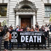 Climate change activists stage a protest outside the Treasury building in central London on April 25 during environmental protests by the Extinction Rebellion group. | AFP-JIJI