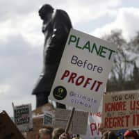 Climate change demonstrators hold banners in front of a statue of Winston Churchill during a protest near Parliament in London on April 12. | AP