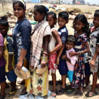 Children line up on Sunday to collect food in Puri, in the eastern Indian state of Odisha, following Cyclone Fani. | AFP-JIJI