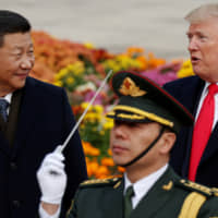U.S. President Donald Trump takes part in a welcoming ceremony with Chinese President Xi Jinping at the Great Hall of the People in Beijing in November 2017. | REUTERS