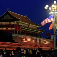 People walk under American and Chinese flags at the Forbidden City during the visit by U.S. President Donald Trump to Beijing in November 2017. | REUTERS