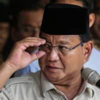 Indonesia's presidential challenger Prabowo Subianto adjusts his glasses during a news conference in Jakarta on Tuesday. | AFP-JIJI