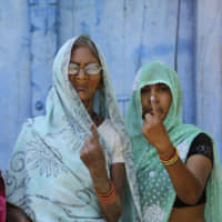 Indian women display indelible ink marks on their fingers after voting in the Uttar Pradesh village of Karari on Monday. | AP