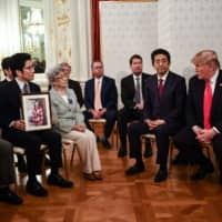 During a meeting in Tokyo on Monday, U.S. President Donald Trump speaks to the relatives of Japanese nationals abducted by North Korea decades ago as first lady Melania Trump and Prime Minister Shinzo Abe look on. | AFP-JIJI