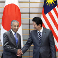 Prime Minister Shinzo Abe greets his Malaysian counterpart, Mahathir Mohamad, at the Prime Minister's Office in Tokyo on Friday. | AFP-JIJI