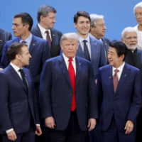 U.S. President Donald Trump and Prime Minister Shinzo Abe prepare for a photo-op during the Group of 20 summit in Buenos Aires last November. | REUTERS / VIA KYODO