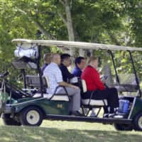 Prime Minister Shinzo Abe drives a golf cart with U.S. President Donald Trump at the Mobara Country Club in Mobara, Chiba Prefecture, during a round of golf Sunday morning. | POOL / VIA KYODO