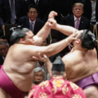 U.S. President Donald Trump attends the Summer Grand Sumo Tournament with Prime Minister Shinzo Abe and first lady Melania Trump at Ryogoku Kokugikan on Sunday in Tokyo.  | AP