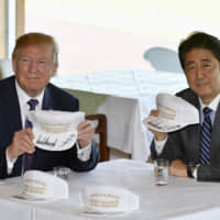 Trump and Abe pose after signing hats reading 'Donald and Shinzo, Make Alliance Even Greater' at the Kasumigaseki Country Club in Kawagoe, near Tokyo, on Nov. 5. | AP