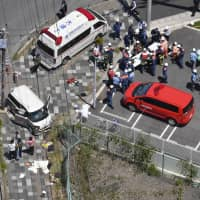 First responders tend to those injured in a car accident in Otsu, Shiga Prefecture, on Wednesday, in which a group of children were hit. | KYODO