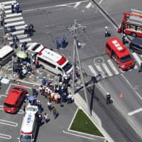 Police and rescue workers scramble to help the injured after a group of preschool children and their teachers were hit in a car accident in Otsu, Shiga Prefecture, on Wednesday morning. | KYODO