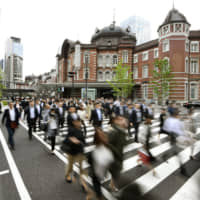 People walk at a crossing near Tokyo Station on their way to work on Tuesday, the first working day of the Reiwa Era following the unprecedented 10-day Golden Week holiday. | KYODO