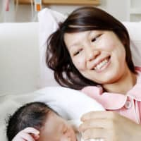 Michiko Fumita holds her baby girl who was born Wednesday morning, the first day of Reiwa, at a hospital in Toda, Saitama Prefecture. | KYODO