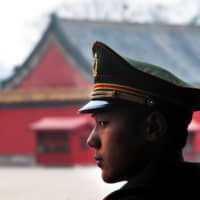 A Chinese soldier guard stands inside the Forbidden City in Beijing in this file photo taken in 2009. Tokyo has reportedly asked Beijing to have a meeting of foreign and defense ministers of the two countries. | GETTY IMAGES
