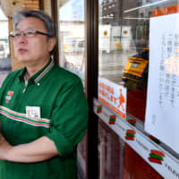 Mitoshi Matsumoto speaks in front of his 7-Eleven store in Higashiosaka, Osaka Prefecture, which has a sign at the entrance saying the store's operating hours have been reduced since February. | CHUNICHI SHIMBUN