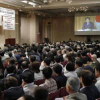 A video message from Prime Minister Shinzo Abe is shown Friday at a forum in Tokyo hosted by a conservative grassroots group aligned with Japan Conference (Nippon Kaigi). | KYODO