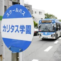 A school bus for Caritas Elementary School arrives a stop in Kawasaki on Wednesday morning, where its pupils and their parents were attacked. | KYODO