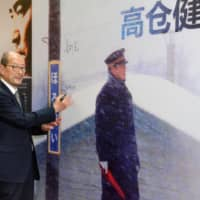 Film director Yasuo Furuhata, who died on May 20, is seen signing a poster promoting his film 'Poppoya' (Railroad Man) at a cinema in Shanghai in June 2015. | KYODO