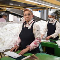 Mikiko Kuzuno, 75, works at a plant run by Tokyo Suzuran K.K. in Warabi, Saitama Prefecture. She has been employed by the company, which launders and packages steamed hand-towels provided to customers at restaurants, for three years now. | BLOOMBERG