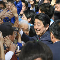 Prime Minister Shinzo Abe greets people after delivering a speech in Osaka in April ahead of Lower House by-elections.   KYODO