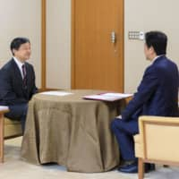 Emperor Naruhito receives his first briefing on domestic and international matters from Prime Minister Shinzo Abe at the Imperial Palace in Tokyo on Tuesday. | IMPERIAL HOUSEHOLD AGENCY / VIA KYODO