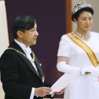 Emperor Naruhito makes his first speech at the Imperial Palace in Tokyo on Wednesday, as his wife, Empress Masako, stands by his side. | POOL / VIA KYODO