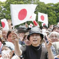 Well-wishers wave flags during Emperor Naruhito's first public appearance at the Imperial Palace in Tokyo on Saturday. More than 140,000 people are estimated to have taken part in celebrations.   KYODO