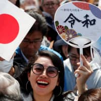 A woman waves a Japanese flag and fans featuring the name of the new imperial era, Reiwa, on them before the first public appearance of Emperor Naruhito and Empress Masako at the Imperial Palace in Tokyo on Saturday.   REUTERS