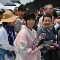 Women wear kimono during Emperor Naruhito's first public appearance at the Imperial Palace in Tokyo on Saturday. More than 140,000 people are estimated to have taken part in celebrations.   AFP-JIJI