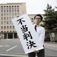 A plaintiffs' lawyer holds up a sign reading 'unjust ruling' in front of the Sendai District Court on Tuesday after the court dismissed a damages suit filed by two women who underwent forced sterilization.  | KYODO