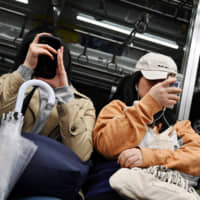 People use smartphones in a subway train in Tokyo on May 4. The government is pressuring the leading mobile phone carriers in hopes of reducing consumer fees and reinvigorating competition in the industry. | AFP-JIJI