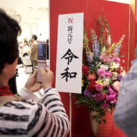Customers use mobile phones to photograph a sign promoting the new Reiwa Era at a Matsuya Co. department store in Tokyo's Ginza district on May 1. | BLOOMBERG