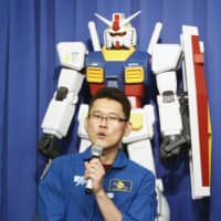 Japanese astronaut Norishige Kanai briefs reporters at a news conference in Tokyo on Wednesday about the Tokyo 2020 organizers' plan to launch model robots from the 'Mobile Suit Gundam' anime series into space aboard a satellite that will broadcast messages of support to athletes. | KYODO