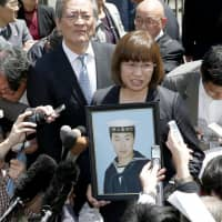 The mother of a Maritime Self-Defense Force member who killed himself after being bullied by a superior officer speaks to reporters in April 2014 after the Tokyo High Court ordered the government and the officer to pay damages. | KYODO